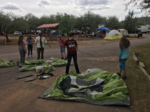 image: kids setting up their tents