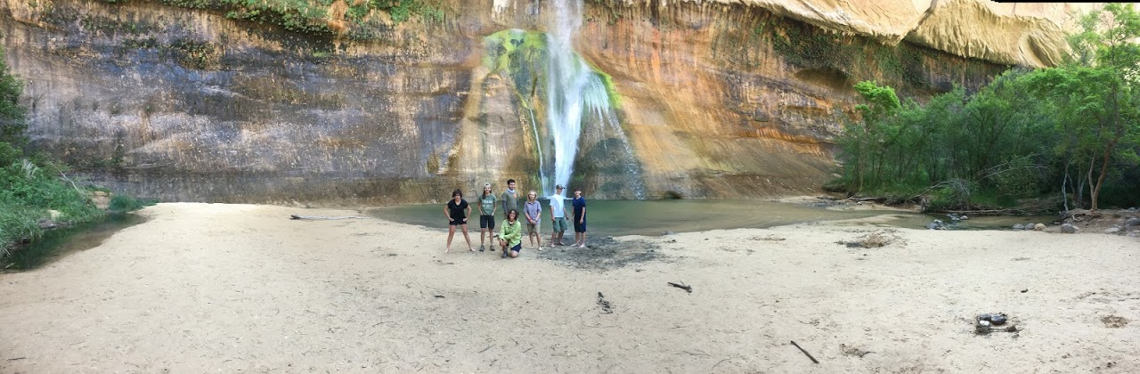 Kids standing in front of a waterfall at calf creek - Escalante Trip 2019