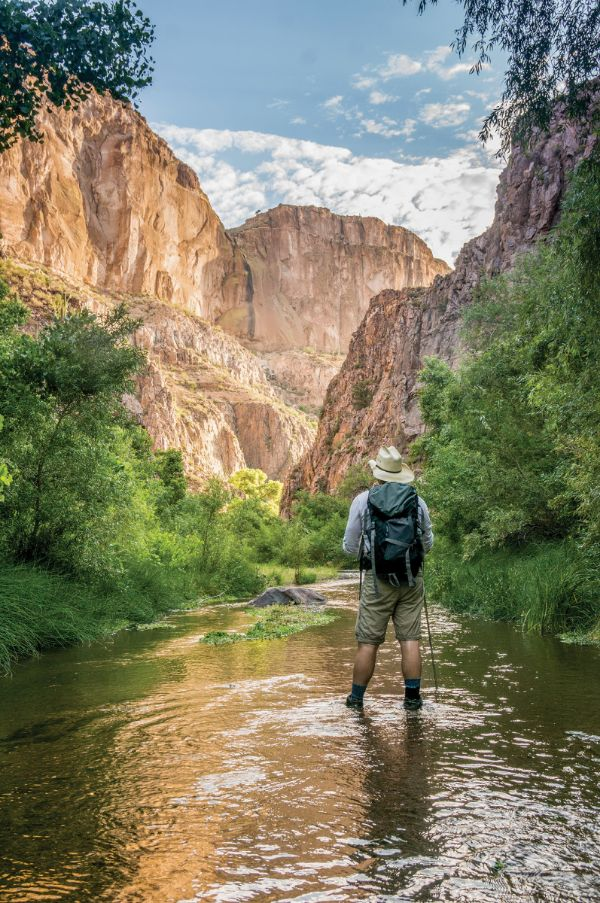 backpacking man standing in creek