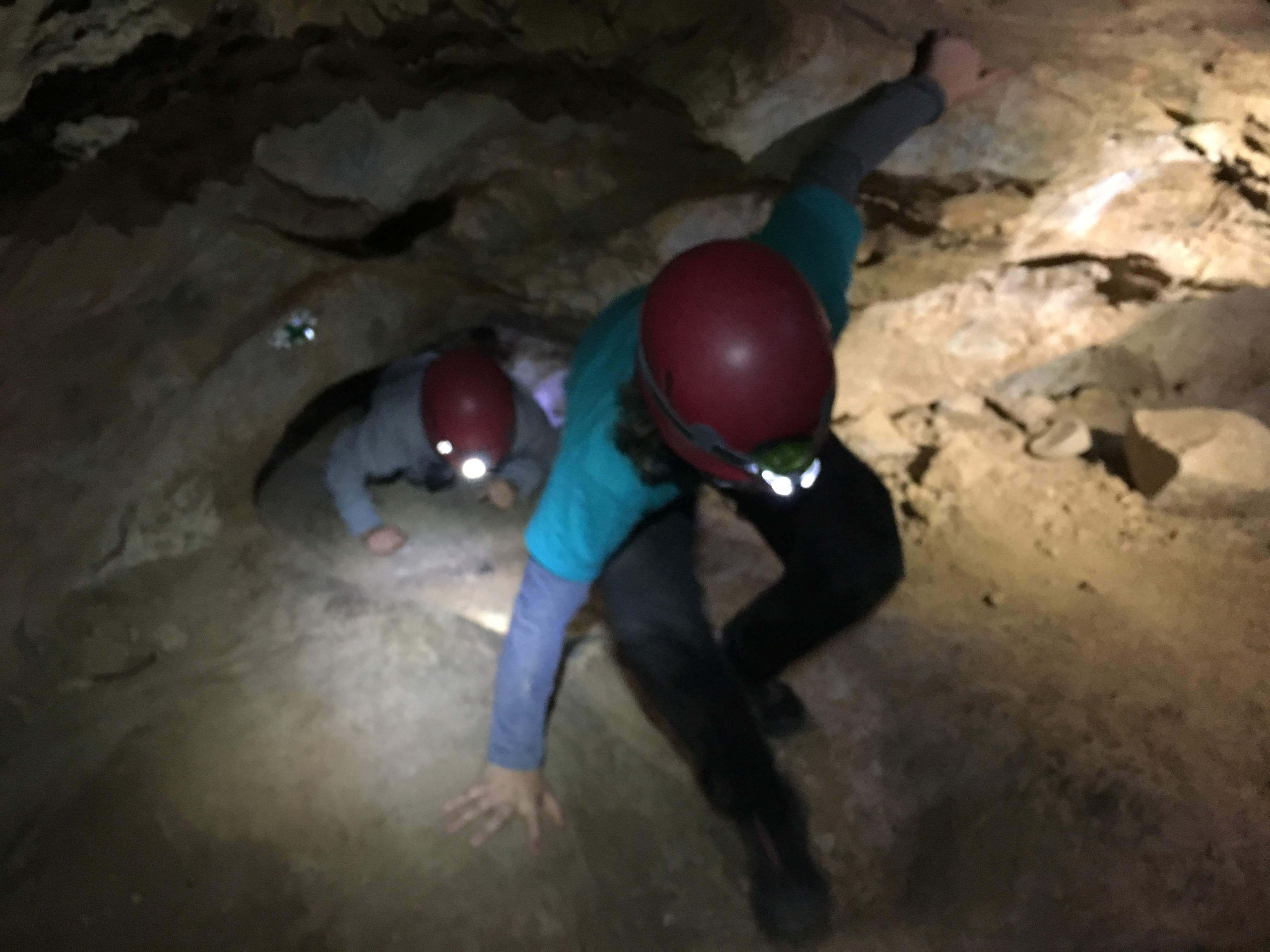 Image: kid climbing though a dark cave